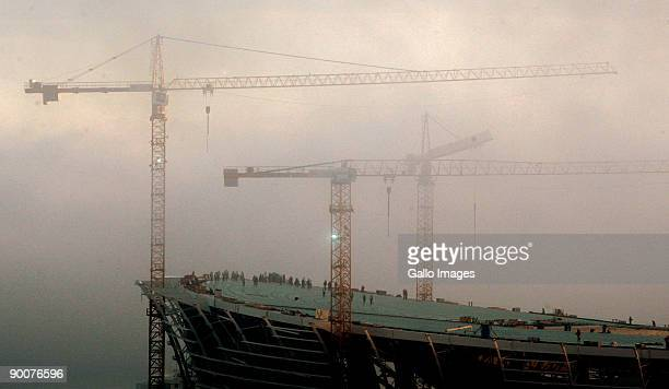 Construction cranes towering over the Green Point Stadium in Cape Town, South Africa, hovers in a bank of fog on 25 August 2009 in Cape Town, South...
