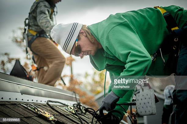construction crew installing solar panels on a house - heshphoto stock pictures, royalty-free photos & images