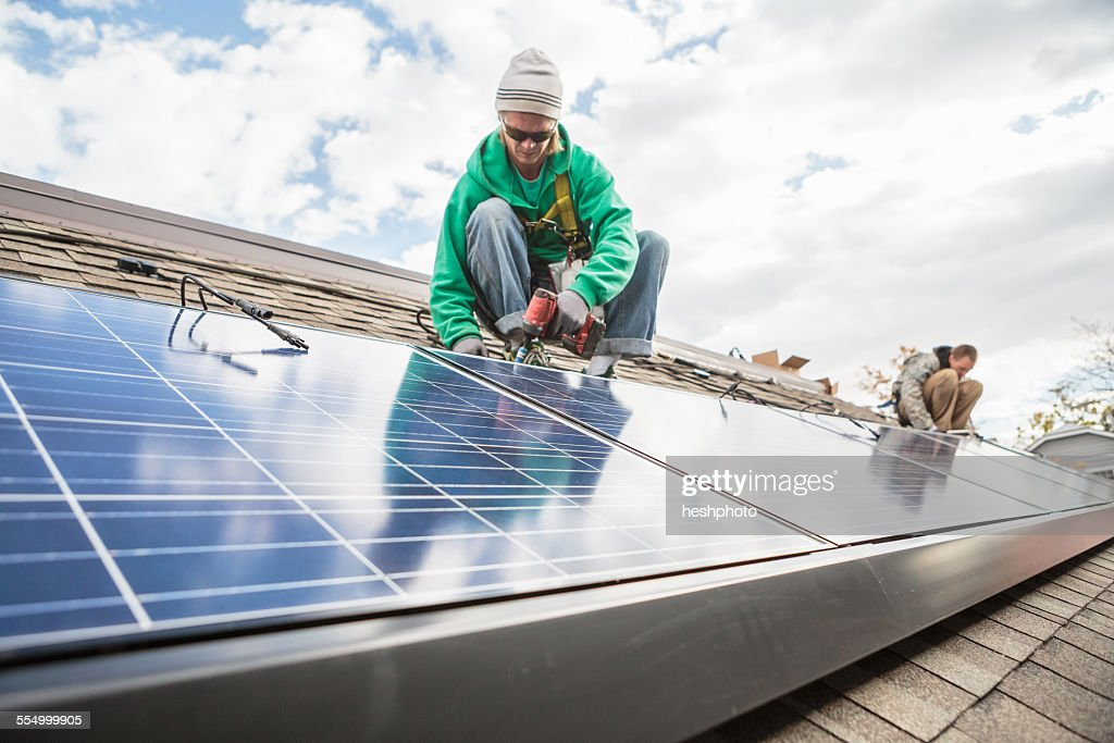 Construction crew installing solar panels on a house : Stock Photo
