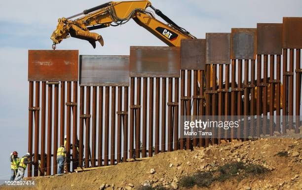 A construction crew installs new sections of the USMexico border barrier replacing smaller fences on January 11 2019 as seen from Tijuana Mexico...