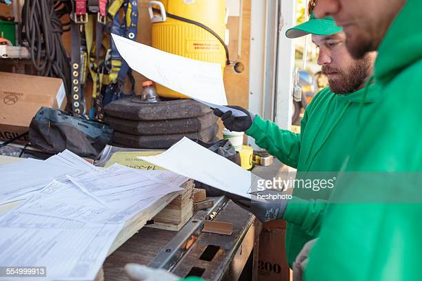 construction crew looking at paperwork for solar panel installation - heshphoto stock pictures, royalty-free photos & images