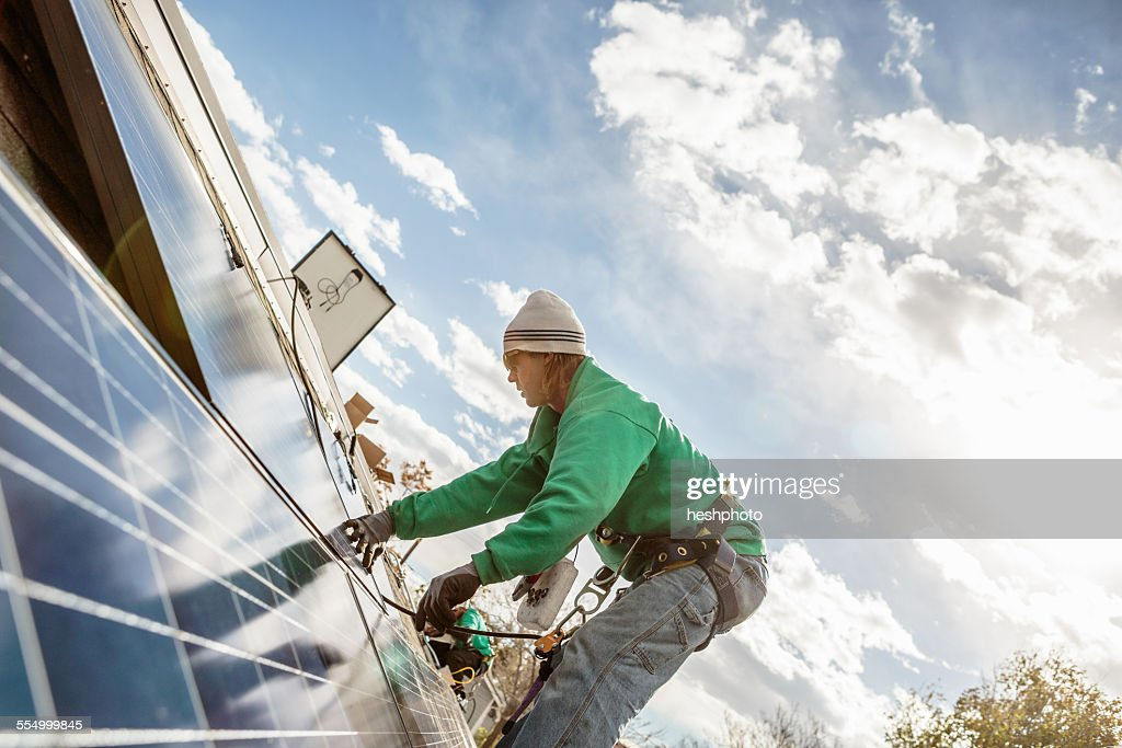 Construction crew member installing a solar panel on a house : Stock Photo