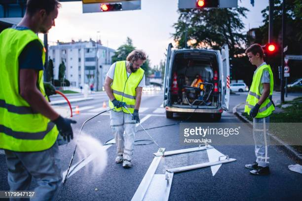 construction crew member spray painting turn arrow at dusk - dividing line road marking stock pictures, royalty-free photos & images