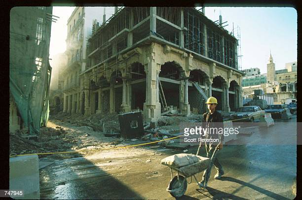 A construction crew worker pushes a wheelbarrow at a site September 24 1997 in Beirut Lebanon The Bourse de Beyrouth was closed in 1983 during...