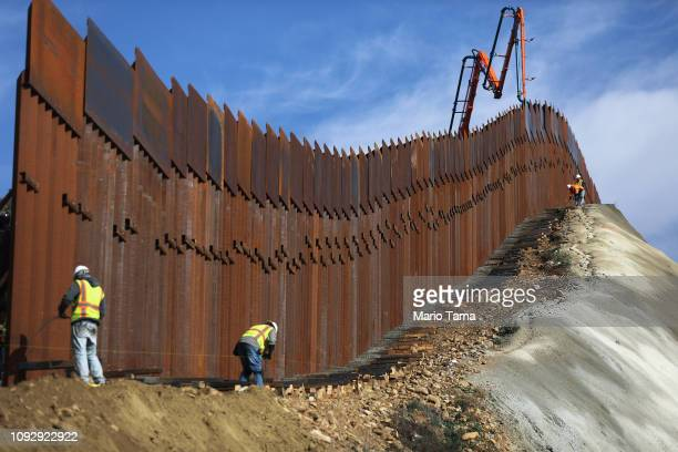 A construction crew works as new sections of the USMexico border barrier are installed replacing smaller fences on January 11 2019 as seen from...