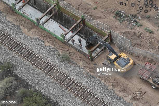 A construction crew works on a new section of the USMexico border fence on August 1 2017 as seen from a US Customs and Border Protection helicopter...