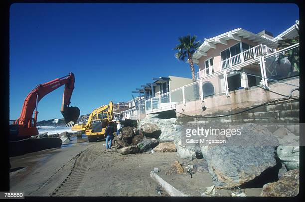 A construction crew works to protect beachfront homes with huge rocks February 9 1998 in Los Angeles CA Storms caused by El Nino lead to mudslides...