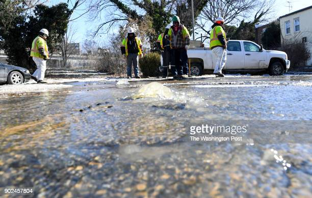 Construction crews from Fort Myer Construction Corportation and District of Columbia Water and Sewer Authority work on a broken water main pipe on...