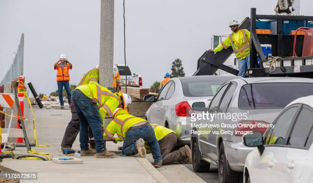 Construction crews install a light pole on the new Slater Avenue bridge over the 405 freeway in Fountain Valley on Wednesday, August 28, 2019. The...