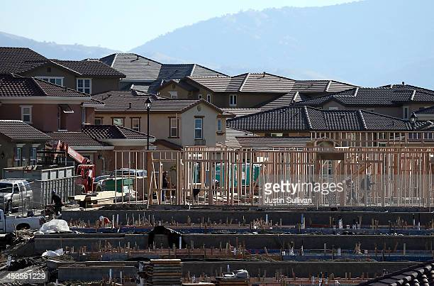 Construction crews work on new homes at a housing development on December 4 2013 in Dublin California According to a Commerce Department report sales...