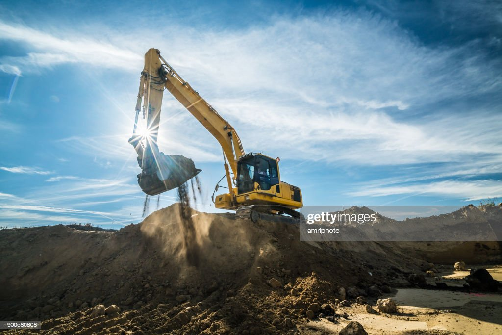 Construction - digger working at building site on sunny day : Stock Photo