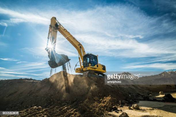 construction - digger working at building site on sunny day - digging stock pictures, royalty-free photos & images