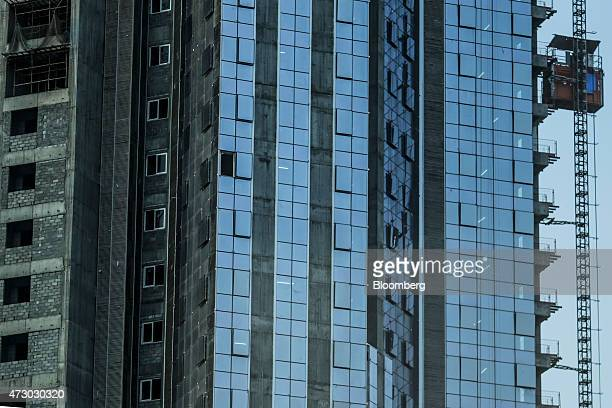 A construction elevator travels up the exterior of an Indiabulls Real Estate Ltd commercial building construction site in the Lower Parel area of...