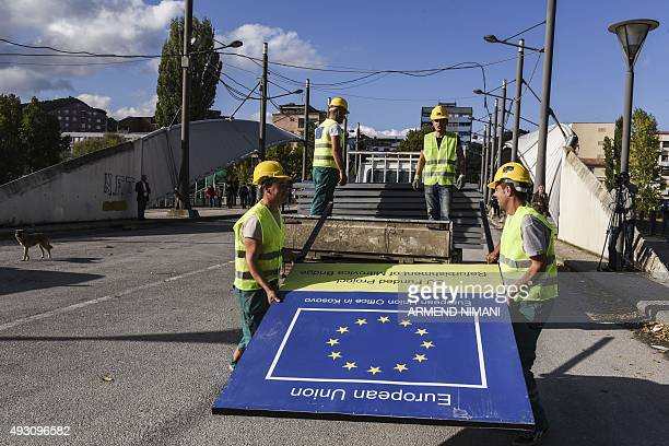 Construction employees unload metal panels during the reconstruction of the main bridge of the divided town of Mitrovica on October 17 2015 Kosovo's...