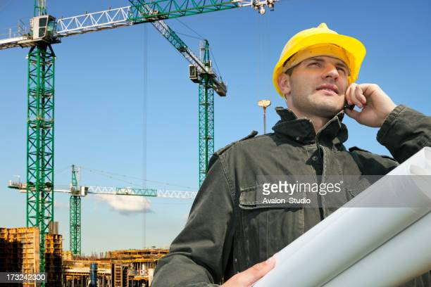 Construction engineer on the construction site talking on the phone.