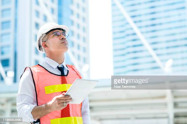 construction engineer wearing protective helmets and vests discussing project details at construction site. - foreperson stock pictures, royalty-free photos & images