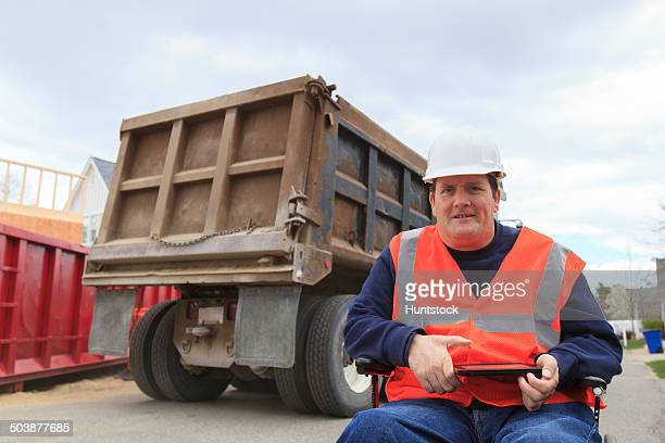 Construction engineer with spinal cord injury holding tablet on site