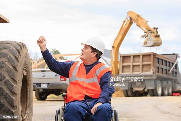 Construction engineer with spinal cord injury talking with front end loader operator