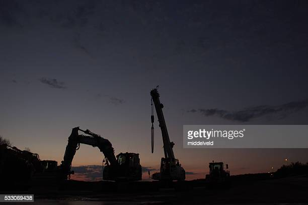 Construction equipment in silhouette at sunset