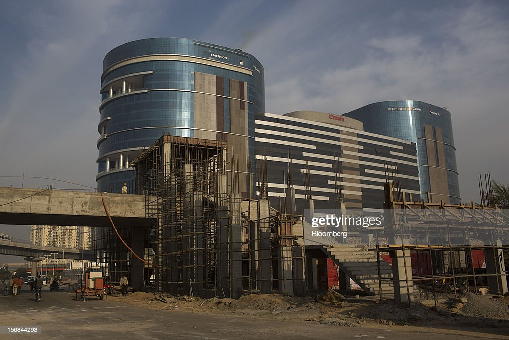 Construction for a new Rapid MetroRail Gurgaon Ltd. station takes place next to DLF Building 5 in DLF Cyber City in Gurgaon, India, on Wednesday, Nov. 21, 2012. Indian Prime Minister Manmohan Singh aims to spur spending on infrastructure to revive a faltering economy and tackle bottlenecks contributing to one of Asia's highest inflation rates. Photographer: Brent Lewin/Bloomberg via Getty Images