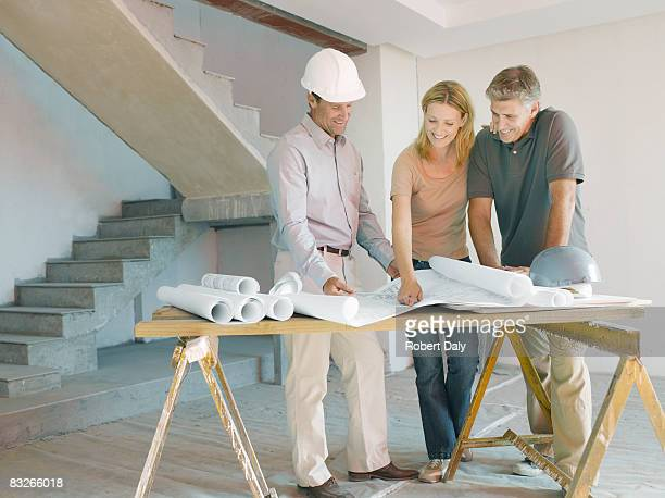 construction foreman explaining blueprints to couple - real estate developer stock pictures, royalty-free photos & images