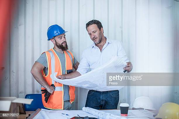 construction foreman looking over blueprint with worker at desk in portable cabin - portable information device imagens e fotografias de stock