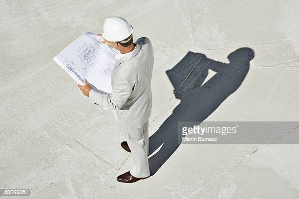 Construction foreman reading blueprints on construction site