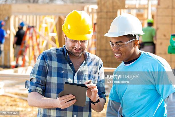Construction foreman uses digital tablet