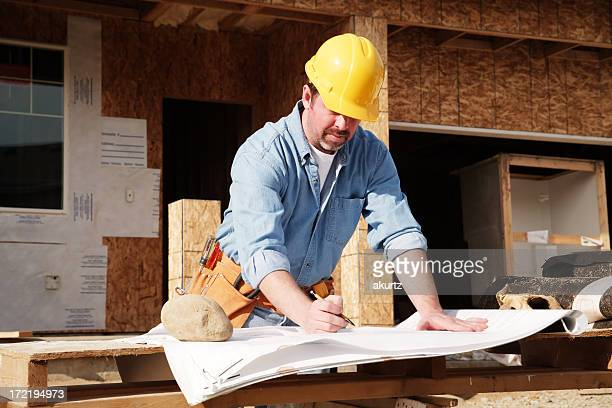 A construction foreman verifying progress on the plans