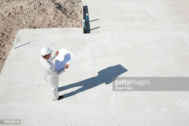Construction foreman viewing blueprints at construction site