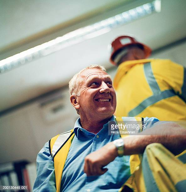 Construction foreman wearing neon jacket in office, low angle view