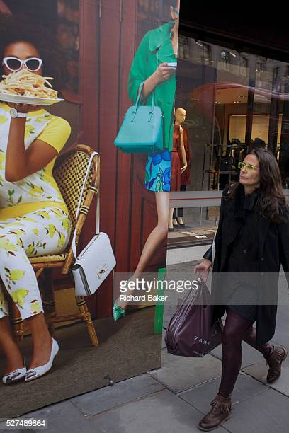 Construction hoarding for forthcoming Kate Spade in Regent Street central London A woman shopper walks beneath the illustration of women outside a...