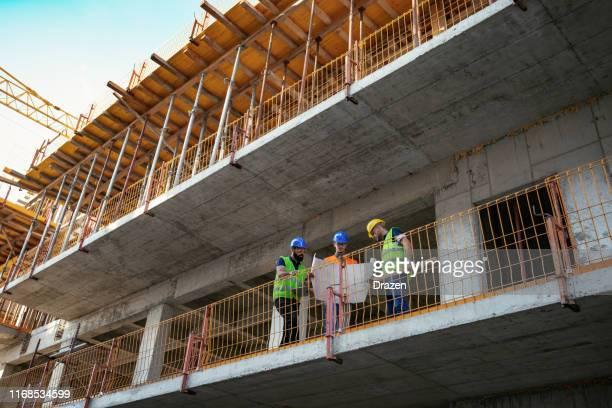 bouwnijverheid-architecten en ingenieurs over voortgangsverslag - bouwwerk stockfoto's en -beelden
