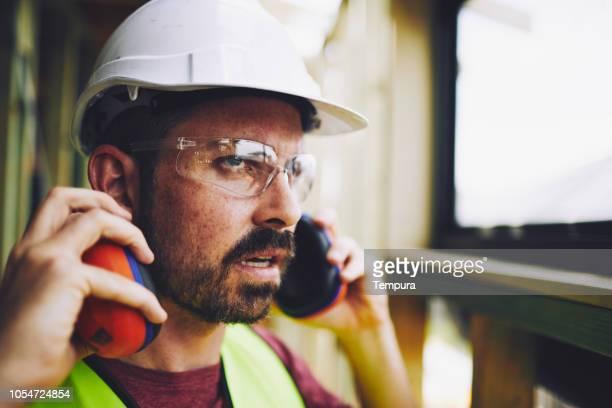 bauarbeiter industrie gehörschutz aufsetzen. - schutzbrille stock-fotos und bilder