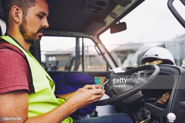 construction industry worker texting on the phone inside a truck. - van stock pictures, royalty-free photos & images