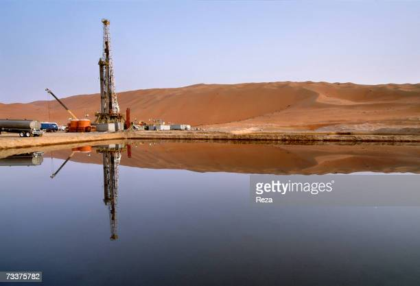 Construction is reflected in a pool at the Saudi Aramco oil field complex facilities at Shaybah in the Rub' al Khali desert on March 2003 in Shaybah...