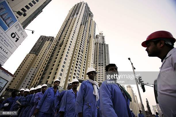 Construction Labourers working in the Dubai Marina area line up to board a bus which will take them back to their labour camp for the night on May 1...