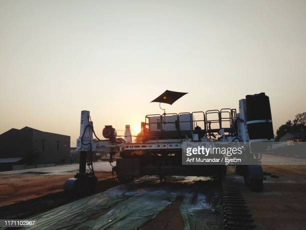 construction machinery on road against clear sky during sunset - munandar stock pictures, royalty-free photos & images
