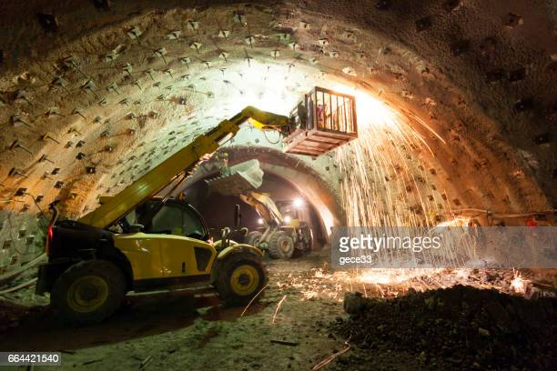 construction machinery working in tunnel construction - underground stock photos and pictures