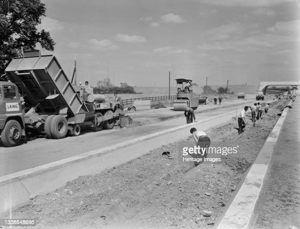 Construction machines laying a dry-lean concrete base in Section D4 of the London to Yorkshire Motorway , as Laing workers dig a trench for central...
