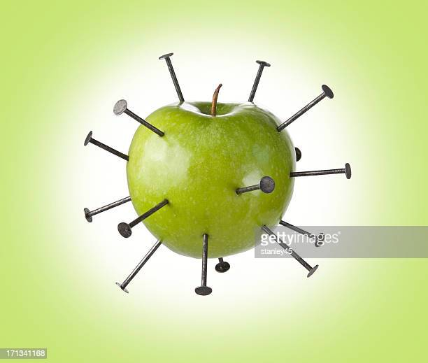 Construction nails piercing a green apple