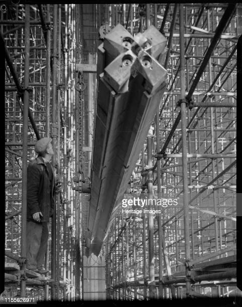 Construction of Coventry Cathedral West Midlands 1960 A man standing on scaffolding watching a nave column being hoisted into position during the...