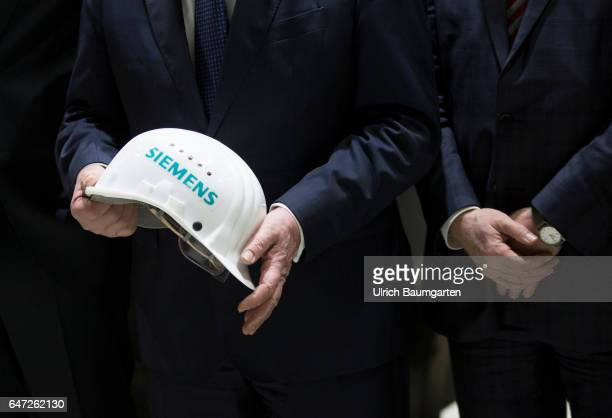 Construction of gas turbines at Siemens AG in Berlin Protective helmet with the inscription Siemens and folded hands