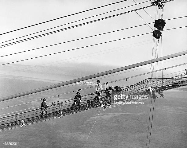 Construction of the Golden Gate Bridge with men on the catwalks working on the cables San Francisco California 1937 Alcatraz Island can be seen in...