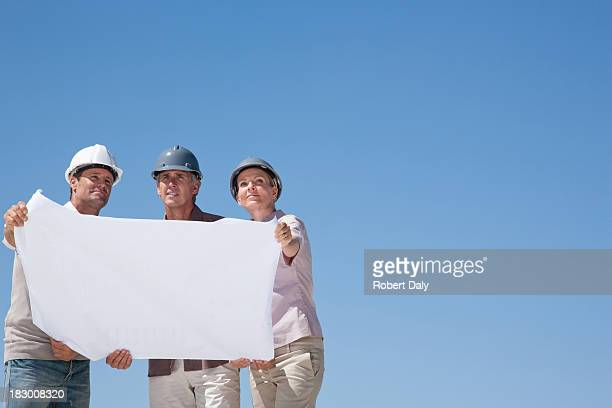 Construction people holding blueprints