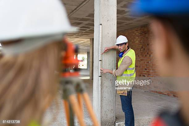 Construction people using transit level mounted on tripod