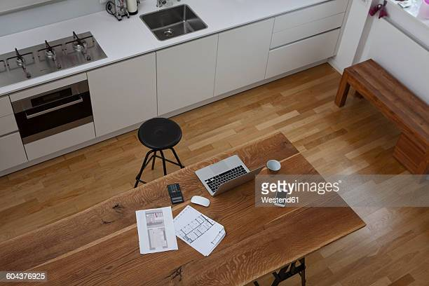 Construction plan, laptop, calculator and cell phone on kitchen table