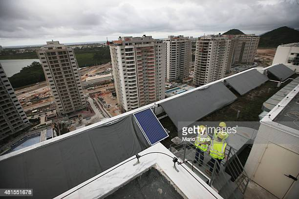 Construction progress takes place on a roof fitted with solar panels during a tour of the Ilha Pura housing complex the future site of the Athletes'...