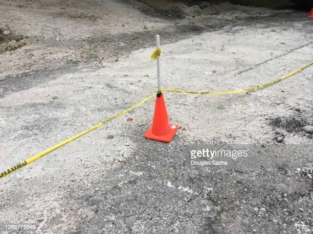 construction safety cone and caution tar creates a barrier - seilabsperrung stock-fotos und bilder