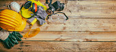 Construction safety. Protective hard hat, headphones, gloves and glasses on wooden background, banner